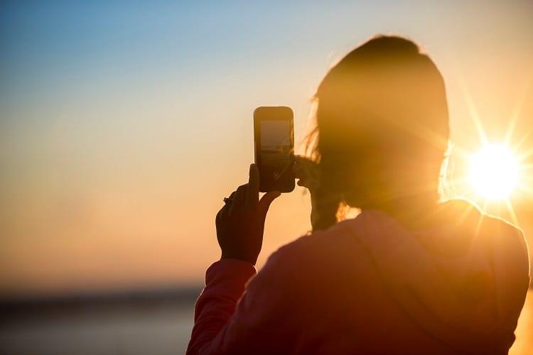 Woman Taking Photo Of The Sun
